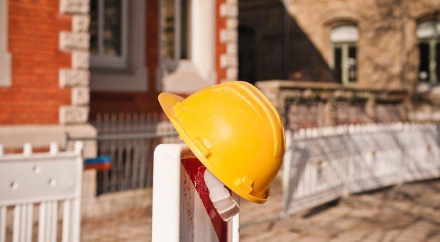 Ein gelber Schutzhelm hängt an einer Warnbake bei Bauarbeiten